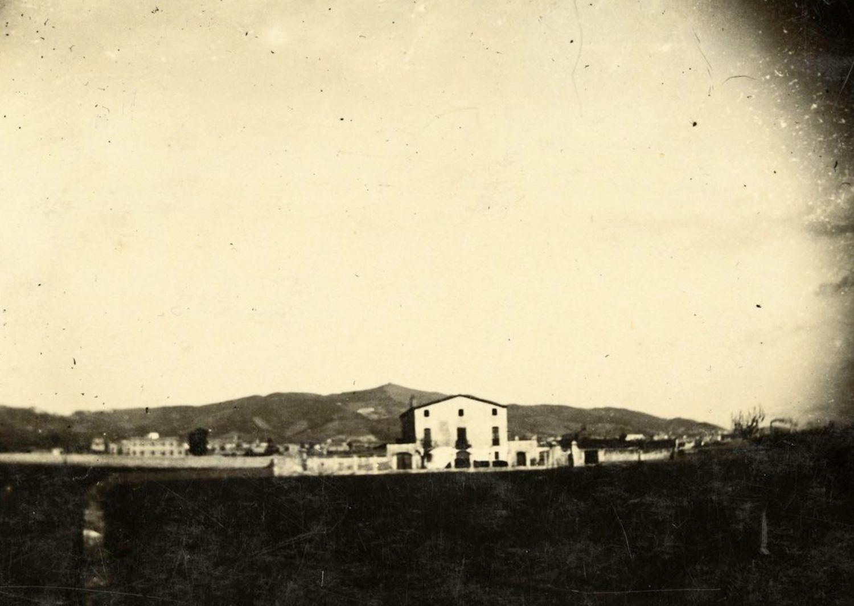 1897 AMDS Terrenys de la masia de can Mantega i al fons edificis del districte de Sants i la serra de Collserola.