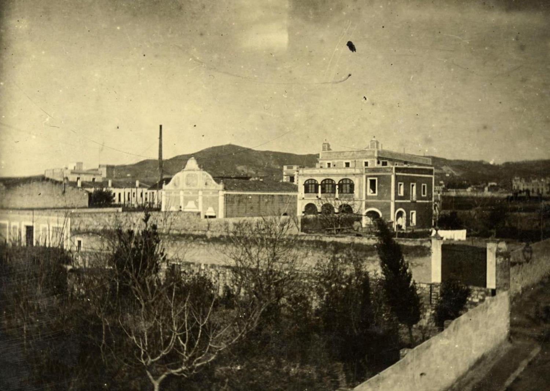 1897 AMDS Vista d_un recinte enmurallat amb arbres davant de can Nicasi, situat al carrer de Miquel Àngel. Al fons, la serra de Collserola.