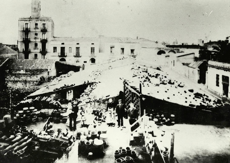 1897 AMDS Vista del taller amb de la Terrisseria Batllori, situada en el carrer de Cros. En primer terme, els propietaris amb els seus fills. Autor Campañà i Mora, Joan