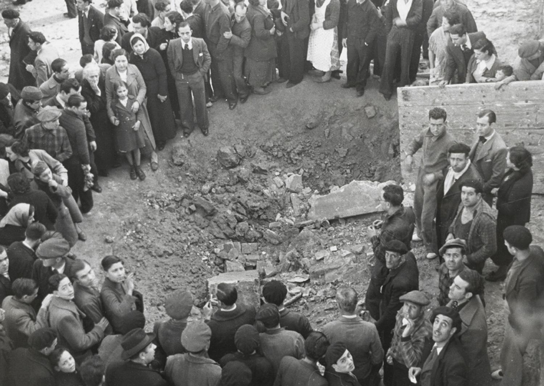 1937 AFB Bombardeig al Poble-sec. Grup de gent observant el forat que ha deixat una bomba. Autor Pérez de Rozas