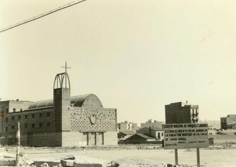 1961 AMDS En primer terme, un rètol situat al carrer de Joan Güell. Al fons, la parròquia de Sant Joan Maria Vianney. Autor Peris i Xancó, Jaume
