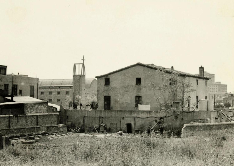 1965 AMDS Vista, des del carrer del Torrent del Perales, del solar situat davant la masia de can Mantega. Al fons, façana lateral i campanar de la parròquia de Sant Joan Maria Vianney.